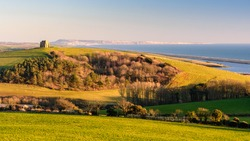 Evening sun illuminates the hilltop St Catherine's Chapel at Abbotsbury in Dorset, with Chesil Beach and the Isle of Portland on the English Channel's Jurassic Coast behind.