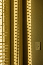 Evening sunlight on window blinds casts a pattern of shadows near a light switch on interior residential wall