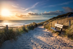 evening sunshine over bench and path to sea beach, Holland