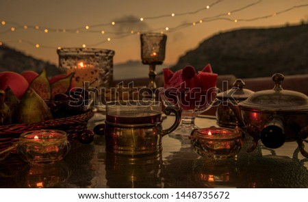 Evening tea. Evening tea with sweets. Very cozy vintage style still life on the background of a garland of light bulbs and the night sky. #1448735672