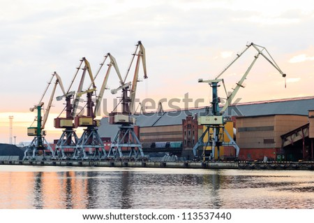 Evening. Tired harbor cranes prepare for a dream