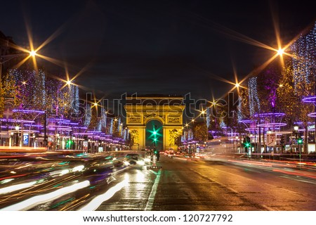 Evening traffic on Champs-Elysees in front of Arc de Triomphe (Paris, France) at Christmas Time