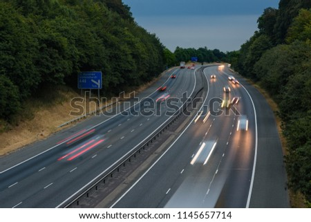 Evening traffic speeds along the M40 motorway in Oxfordshire, UK. Light trails and blurry streaks indicate the fast moving vehicles.