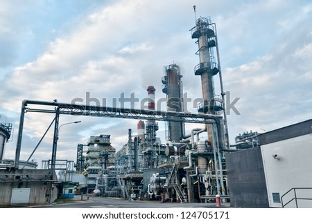 evening view of an oil refinery with cloudy sky and smoking chimneys