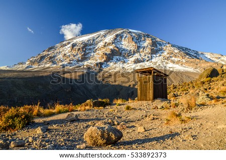 Evening view of Kibo with Uhuru Peak (5895m amsl, highest mountain in Africa) at Mount Kilimanjaro,Kilimanjaro National Park,seen from Karanga Camp at 3995m amsl. Toilet outhouse in foreground.