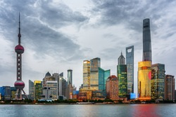 Evening view of Pudong skyline (Lujiazui) in Shanghai, China. Skyscrapers of downtown on waterfront. The Shanghai Tower and the Shanghai World Financial Center (SWFC) are visible at right.