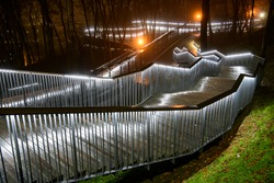 Evening view of the long illuminated stairs in the old park in foggy weather.