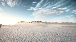 Evening view on small sand dune with green grass. Sandy beach at sea coast. Blue sky with white clouds. Sunset time.