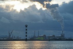 Evening view over the Nieuwe Waterweg to the industry with lighthouse in Europoort