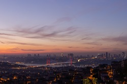 Evening views and orange sky over buildings and streets of Istanbul city. Silhouettes and outlines of skyscrapers against the sunset.