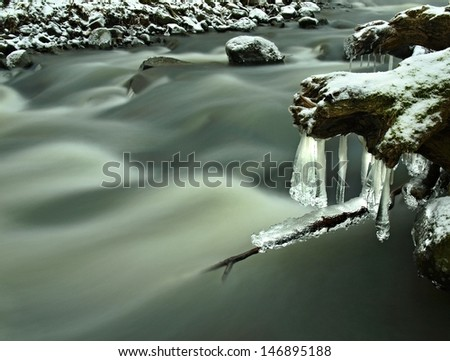 Evening winter view to icicles, icy branches and boulders into chilling stream. Reflections in icicles, blur white foam. - stock photo