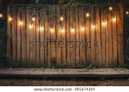 Evening Wooden Stage In The Garden With Lamps For Parties Or Wedding