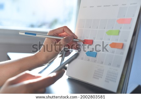 Event planner timetable agenda plan on schedule event. Business woman checking planner on mobile phone, taking note on calendar desk on office table. Calendar event plan, work planning