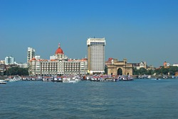 Ever crowded, busy sea front of Mumbai full of luxury yatches and colorful cruise vessels and launches on the backdrop of Mumbai's iconic landmark Gateway of India. Copy space.