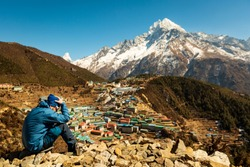 Everest trekking. A man sits on a hill with his head bowed and his arms around him. Altitude sickness. Near the mug. The man in focus. The background is blurred. Namche Bazaar. Nepal
