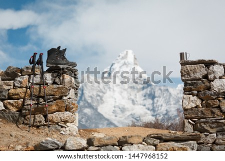 Everest trekking. Trekking boots, trekking poles and a cup in focus. Mountain Ama Dablam in the background is blurred. #1447968152