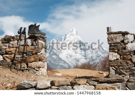 Everest trekking. Trekking boots, trekking poles and a cup in focus. Mountain Ama Dablam in the background is blurred. #1447968158