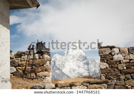 Everest trekking. Trekking boots, trekking poles and a cup in focus. Mountain Ama Dablam in the background is blurred. In the frame on the left wall of the house #1447968161