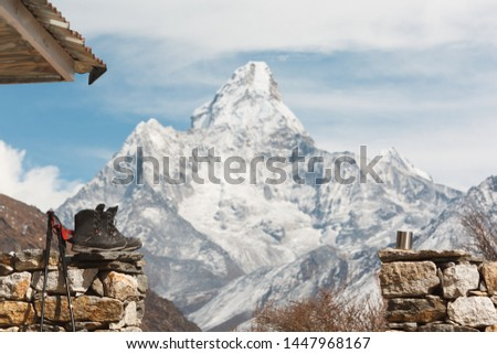 Everest trekking. Trekking boots, trekking poles and a cup in focus. Mountain Ama Dablam in the background is blurred. In the frame on the left wall of the house #1447968167