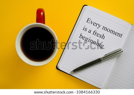 Every moment is a fresh beginning. Inspirational quote on notebook with a mug of coffee. #1084166330