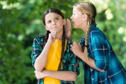 Everybody knows that. Chattering girls summer outdoors. Little child whisper news in friends ear. Top secret. Hearing all chit-chat and gossip. Gossiping and talking. Communication between friends.