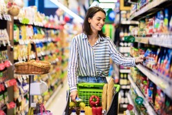 Everyday Shopping Concept. Smiling Young Housewife Pushing Trolley Cart Between Aisles In Grocery Store. Positive Woman Buying Food, Taking Products From Shelf. Consumerism And Lifestyle