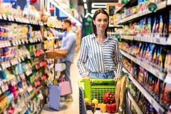 Everyday Shopping. Portrait Of Casual Female Customer Walking With Trolley Cart Between The Aisles In Local Store. Young Woman Buying Healthy Food In Shop, Looking At Shelves, Selective Focus