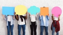 Everyone has own opinion. Teens holding empty colourful speech bubbles