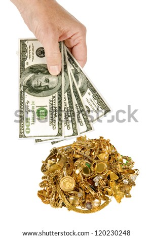 Everyone needs a little extra money.  Sell some of your unwanted jewelry for cash. Hand holding $100 dollar bills with pile of gold jewelry in the background.  Isolated on white.  Studio shot.