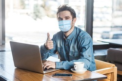 Everything alright! Portrait of satisfied young man with surgical medical mask in blue shirt are sitting and working on laptop, thumb up, looking at camera. indoor working and health care concept.