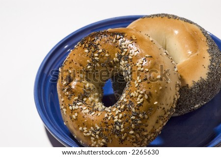 Everything and poppyseed bagels on a blue plate isolated