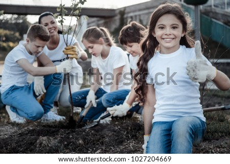 Everything is great. Cheerful cute delighted girl smiling and looking at you while showing OK gesture