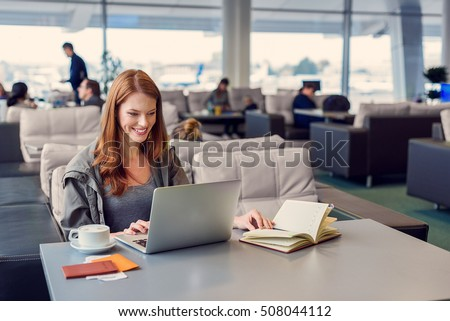 Everything looks great. Beautiful young woman using laptop and notebook while sitting in waiting hall at airport