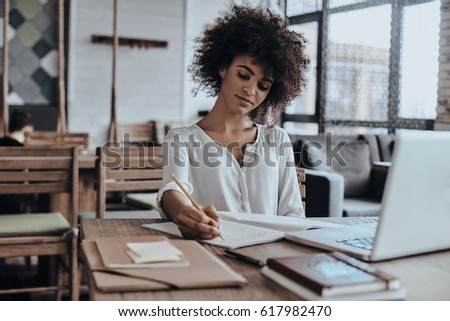 Everything must be planned. Beautiful young African woman in smart casual wear writing something down while sitting in restaurant - Shutterstock ID 617982470