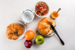 Everything you need for easy and a wholesome breakfast: croissants, jam, granola, oatmeal and dried fruit, fresh fruit (apples, oranges), a cup of tea or coffee