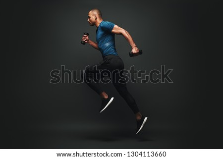 Everything you've ever wanted is on the other side of fear. Dark skinned sportsman jumping over dark background. He is ready to run