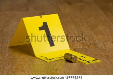 Evidence marker with bullet casing on wooden floor