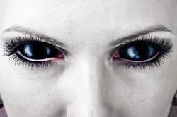 Evil black female alien, vampire or zombie eyes. dirt make up. Macro. Halloween theme