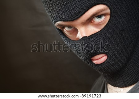 Evil criminal in a mask looking at the viewer; copy space on the left.