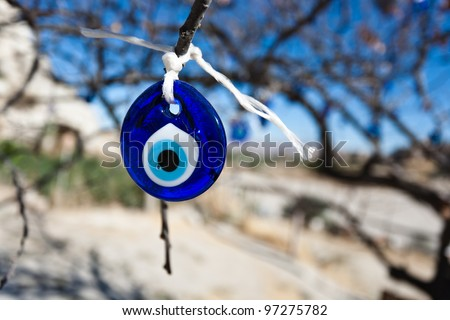 Evil eye charms hang from a bare tree in Cappadocia, Turkey. - stock photo