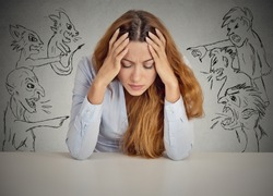 Evil Men pointing at stressed woman. Desperate young businesswoman sitting at desk in her office isolated on grey wall background. Negative human emotions face expression feelings life perception