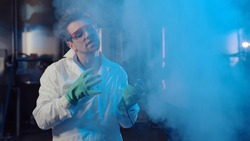 Evil professor pushing remote controller button in large industrial laboratory. Portrait of crazy male scientist in lab coat, protective gloves and goggles releasing blue smoke and laughing