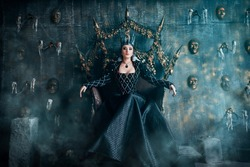 Evil Queen in a black dress. Beautiful girl in the crown sits on the throne
