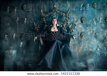 Evil Queen in a black dress. Beautiful girl in the crown sits on the throne Сток-фото ©