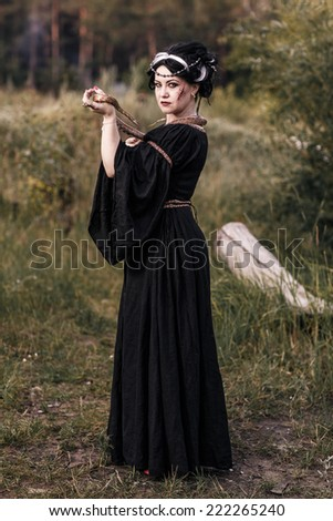 Evil witch woman casting a spooky spell with magic hands. Witchcraft