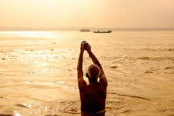 evocative view of old man performing daily puja ritual on calm water of ganges river at sunrise seen from behind, with warm light