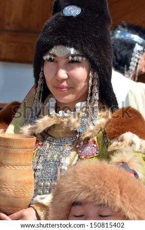 EVOLENE, SWITZERLAND - AUGUST 13: Beautiful Yakutsk dancer holding ceremonial beaker at International Festival of Folklore and Dance from the mountains (CIME) :  August 13, 2013 in Evolene Switzerland