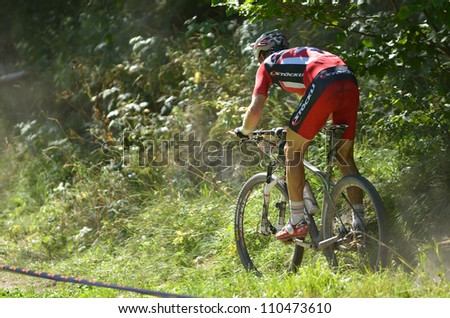 EVOLENE, SWITZERLAND  AUGUST 18: Second placed Urs Huber on a single track  in the world famous Grand Raid mountain bike race:  August 18, 2012 in Evolene Switzerland