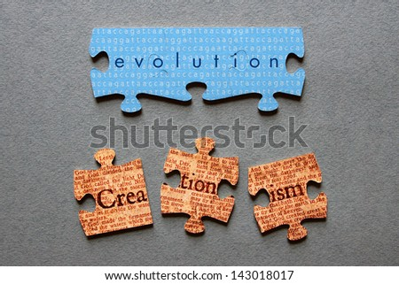 Evolution against background of human genome sequence printed on matched jigsaw pieces with Creationism against background of Genesis text printed on mismatched jigsaw pieces.