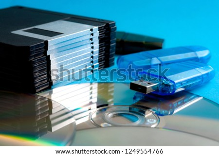 Evolution of data storage technologies and vintage technology concept with close up on a stack of floppy disks, a pile of CD ROMs or DVDs and flash drive memory stick isolated on blue background